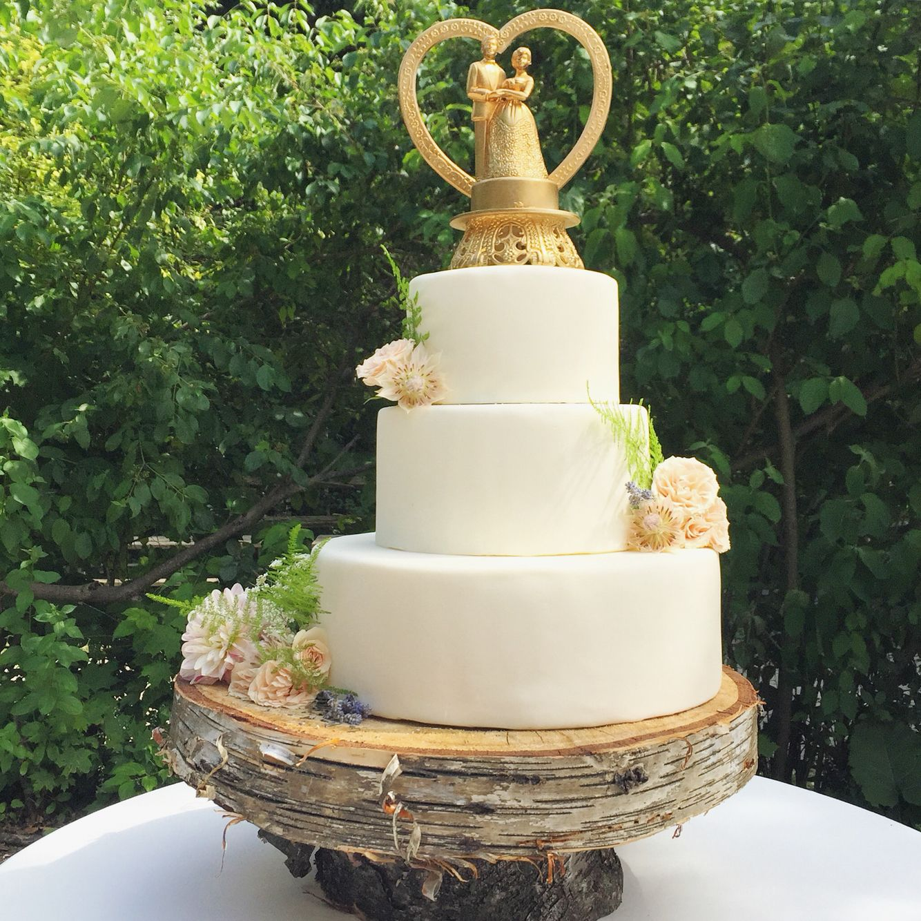Classic wedding cake with real florals displayed on a birch wood