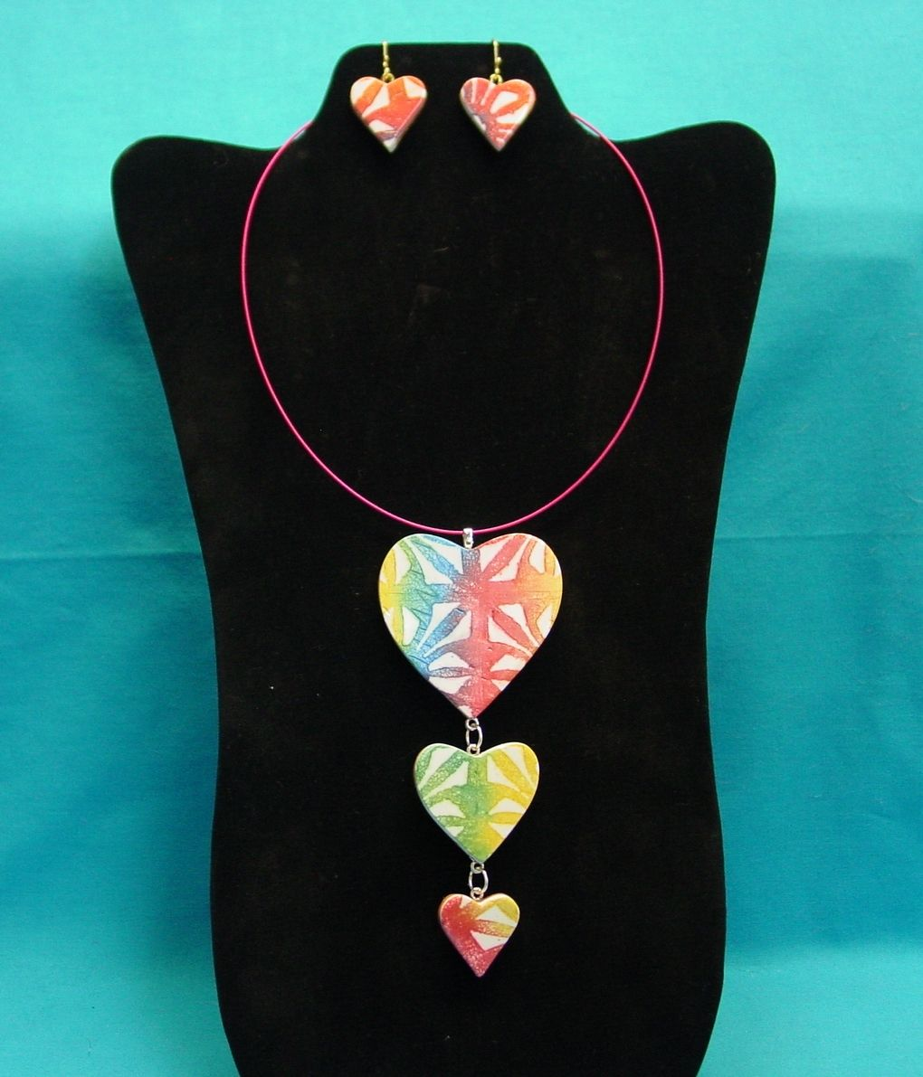 """Hearts in a Row"" made by moi using the Cindy Leitz's tutorial on her Batik technique. Hearts are hung on a red wire necklace with earrings to match."