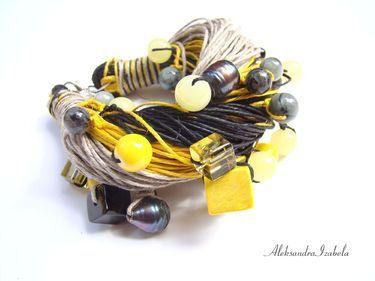 Bransoletkę wykonano z trzech kolorów lnianej przędzy (szary, żółty, czarny).   Zastosowano drewniane kostki, plastikowe kulki, szklane kostki, perły hodowlane, kulki labradorytu, kulki jadeitu, szklane koraliki.    Na innej aukcji oferujemy możliwość zakupienia naszyjnika do kompletu.  Długość bransoletki 22cm + 5cm regulacji łańcuszka.   Uwaga!   Ze względu na kamyczki i dużą objętość bransoletka mieści się na rękę o wymiarze 18-19cm.