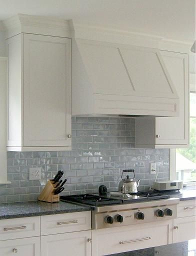 Waterworks grove brickworks backsplash tile in dirty silver with white cabinetry and honed absolute black counters also