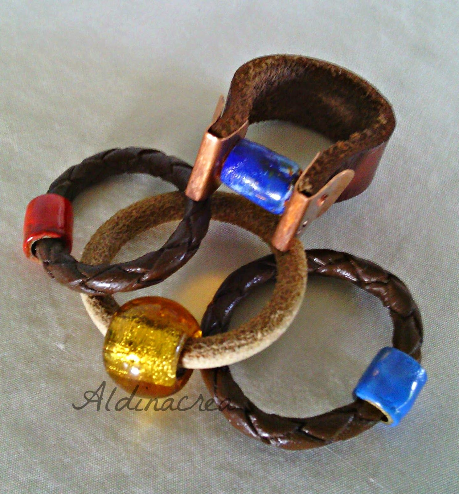 Creazioni e manufatti di Aldina. Anelli in cuoio, rame smaltato e una perla in vetro.