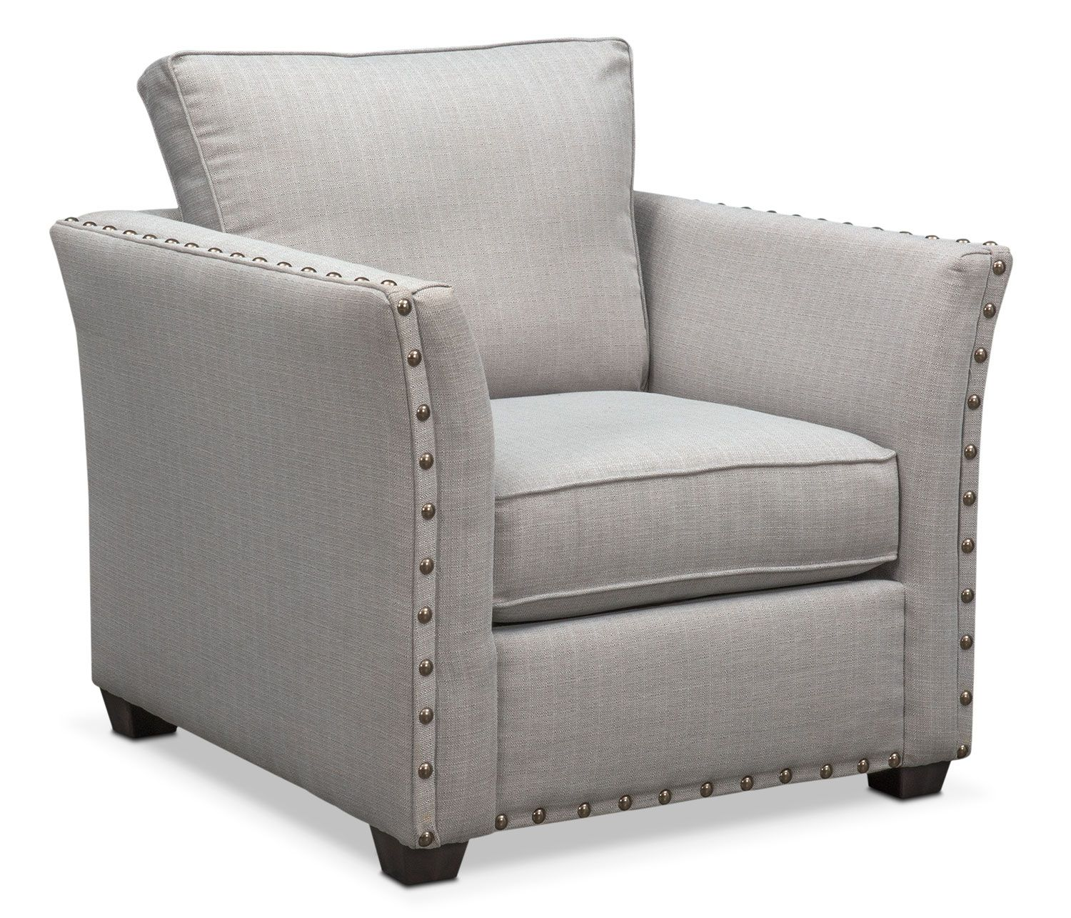 Built to Last. Make a grand statement with the Mckenna chair that exudes classic appeal. With its comfortable seating, this furniture features oversized nailhead trim adorning the ever-stylish flared arms. The relaxing gray fabric is versatile and will match any décor.