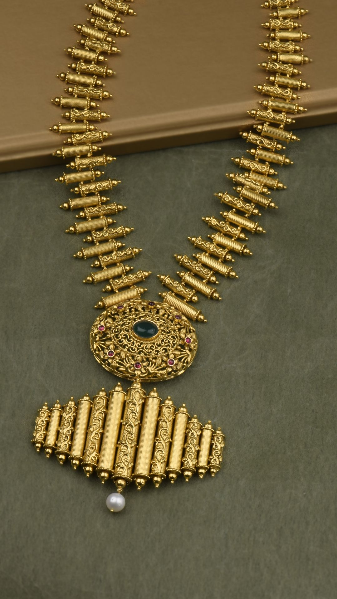Cylindrical gold beads decked with ornamented scrolls adorn the modern necklace