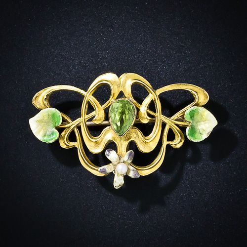 The inspiration for this enchanting Art Nouveau pin and/or watch pin, is mother nature herself. A central glowing peridot leaf is entwined in sinewy golden branches and is further adorned with shaded enamel leaves and a single lavender and seed pearl flower below. A graceful and romantic beauty, circa 1900.