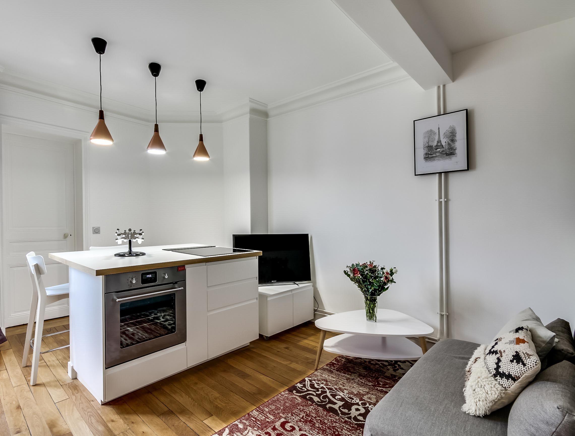 Cuisine ouverte sur coin salon dans appartement entièrement