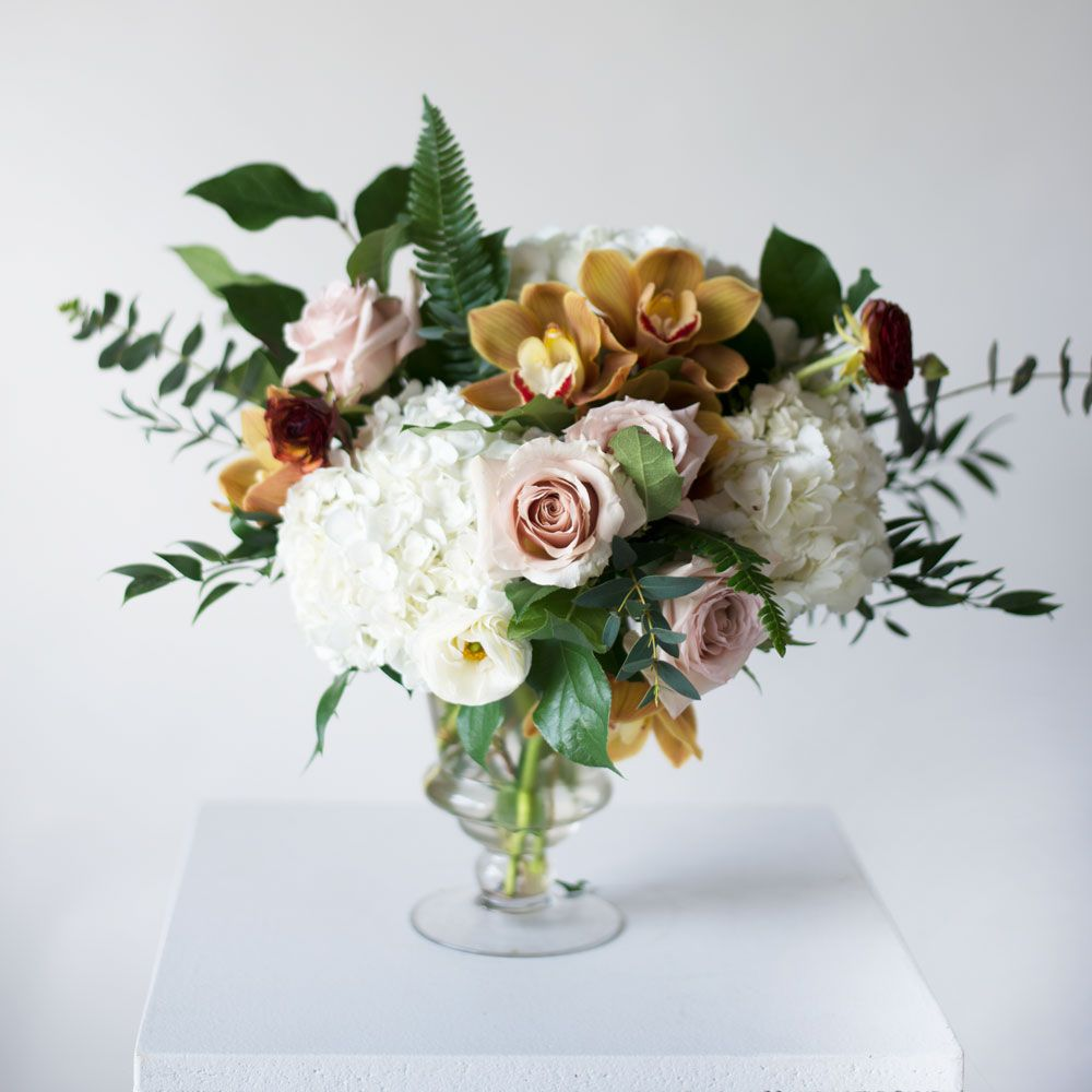 Fall inspired wedding ceremony pedestal arrangements with cymbidium orchids, white hydrangeas, greenery in a clear glass pedestal vase