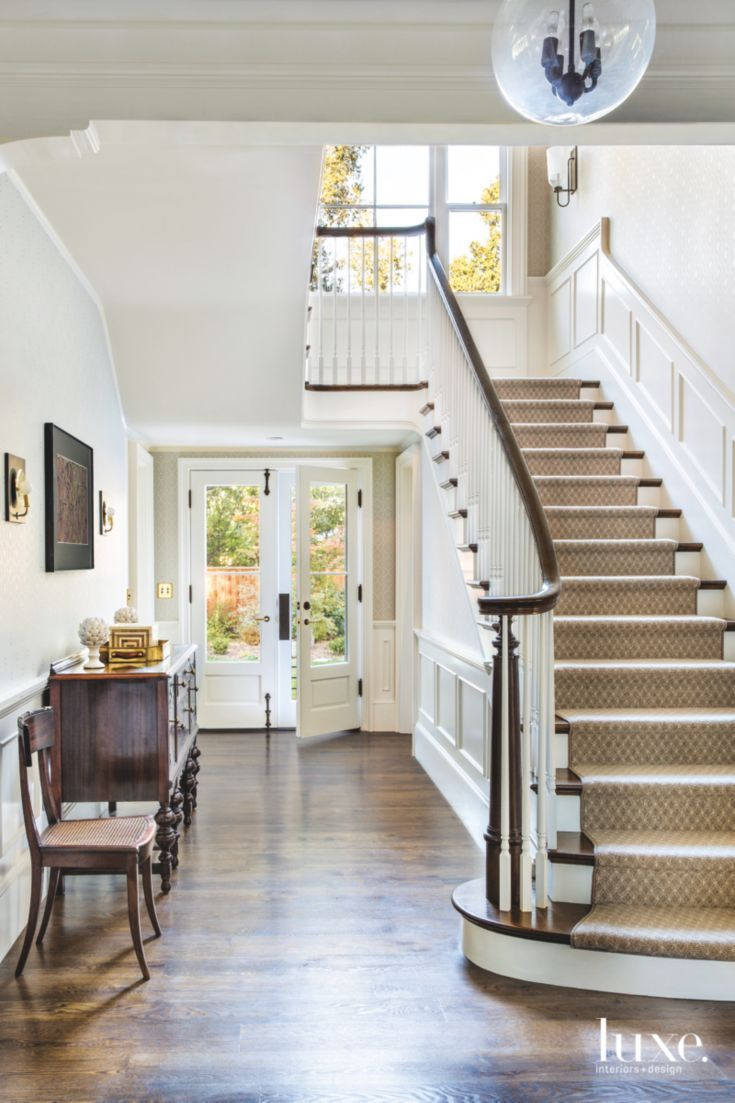 White Foyer With Antique Pieces And Staircasedesigner