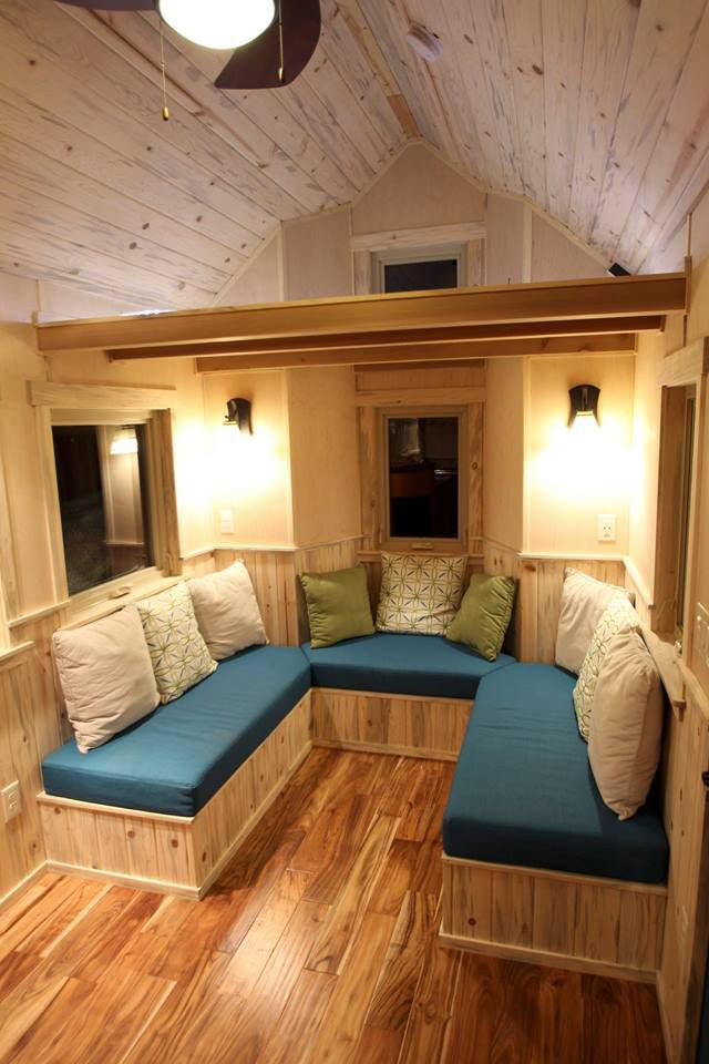 The living room has a large U-shaped sofa that faces the propane ...