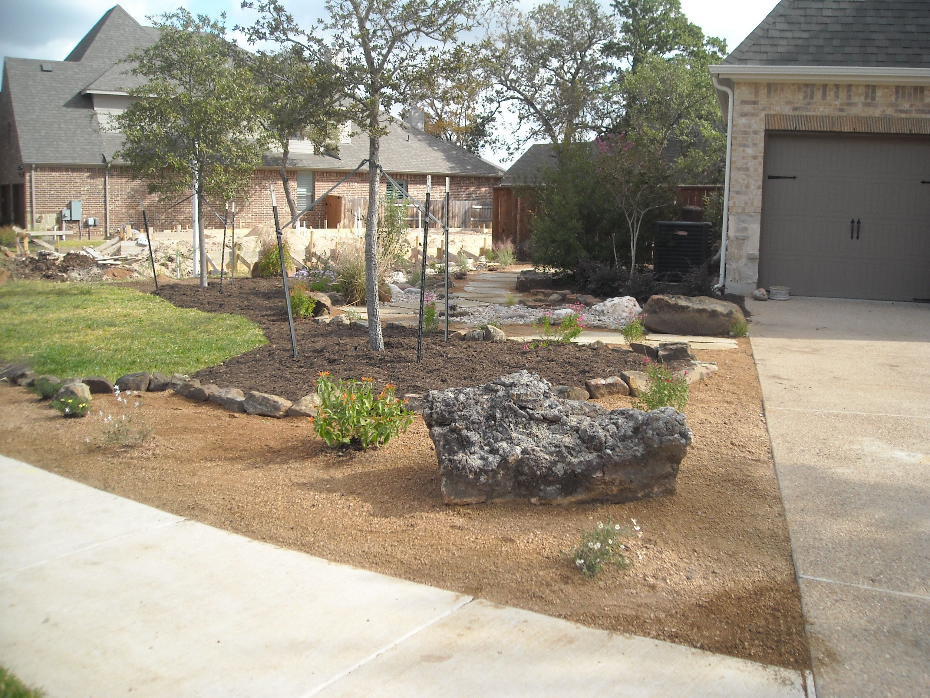 Front yard landscape Xeriscape theme with de posed granite