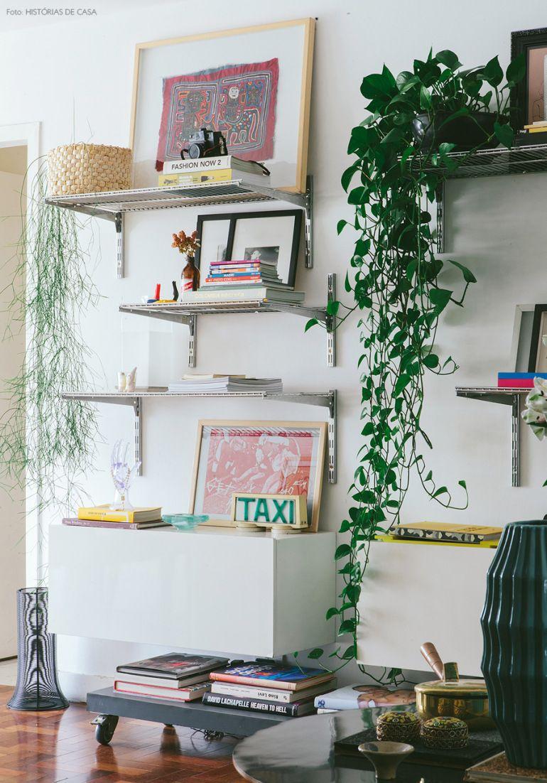 Prateleiras cromadas se tornaram uma pequena estante com objetos diferentes, quadros e plantas.