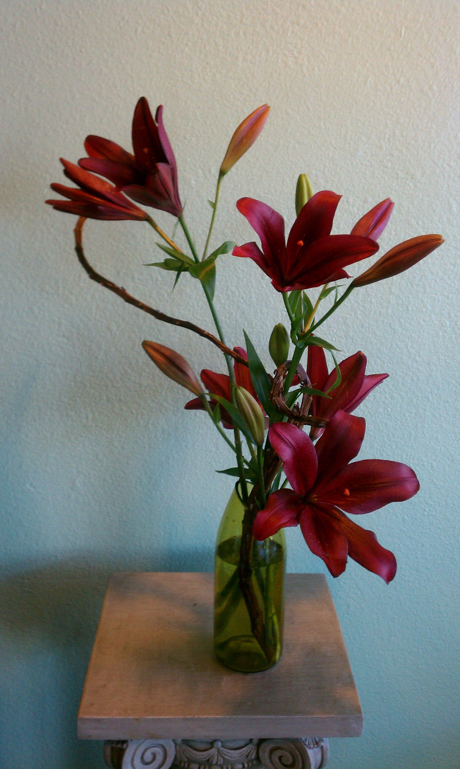 Burgundy Lilies With Fan Tail Pussy Willow In Green Wine Bottle Vase