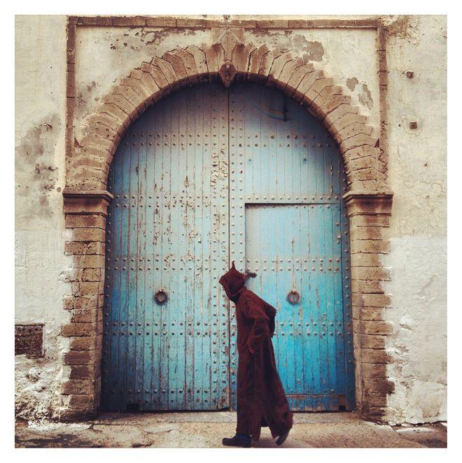 Moroccan man walking next to an old door. Instagram shot
