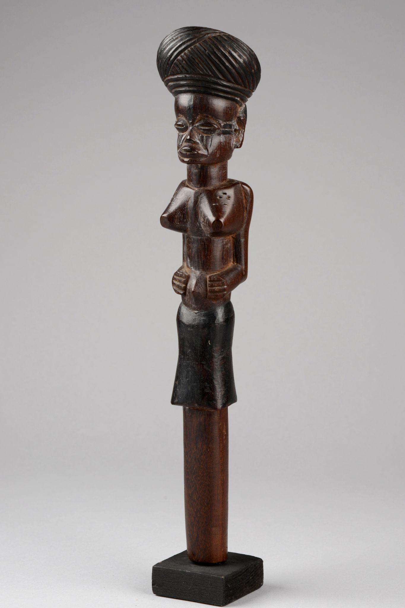 Oberteil eines Würdestabes D. R. Kongo, Chokwe Holz, dunkelbraune Patina, partienweise geschwärzt, bekrönt von weiblicher Figur mit turban-artiger Frisur, min. besch., Sockel