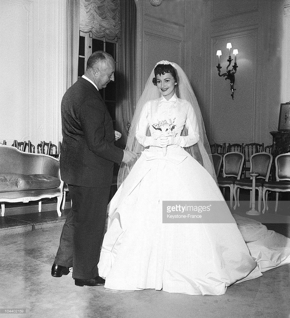 The American actress Olivia de HAVILLAND wearing a Christian DIOR wedding dress for the film LA FILLE DE L'AMBASSADEUR. The fashion designer is making the last alterations.