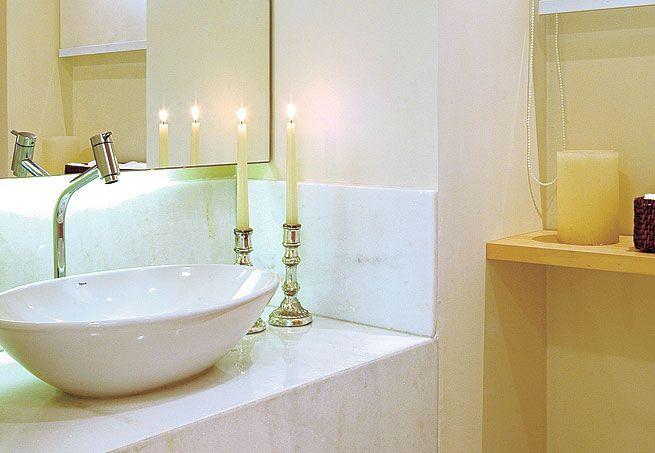 A bancada de mármore branco tem cuba de apoio oval branca e torneira alta de  -> Cuba Banheiro Oval