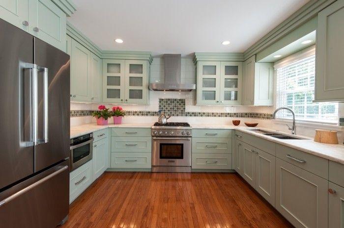 moderne küche in u form mit hellgrünen küchenschränken und boden