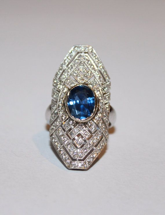 The bright finished mounting has an Art-Deco design and it is circa 1930. Bezel set in the center of the ring is a 2.57 ct. (9.62 x 7.55 x 4.18 mm) oval faceted natural blue sapphire that is of very good color and quality. Bead set in the ring are a total of 108 approximate .015 ct. full cut diamonds that are VS in clarity, G-H provisional in color, and have an approximate 1.65 ct. total weight.