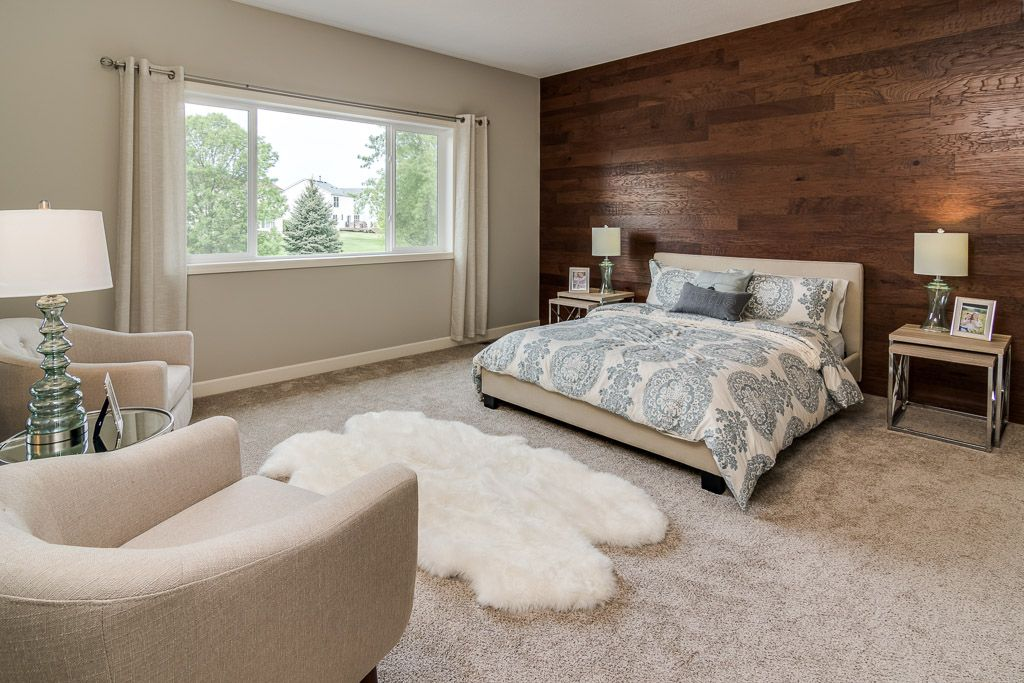 Master Bedroom With Large Window And Accent Wall