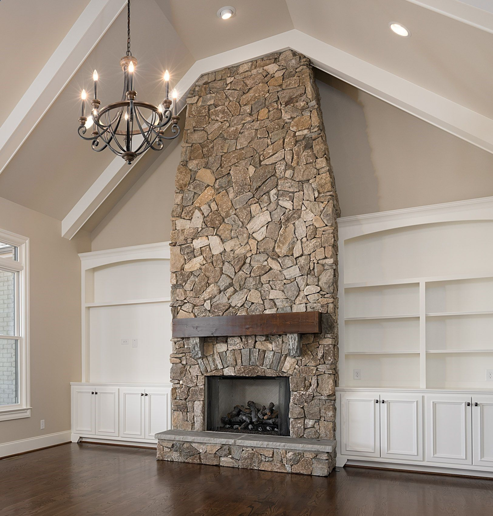 The Perfect Living Room Vaulted Ceilings And An Iron Chandelier Floor To Ceiling Stone Fireplace With Farmhouse Style Mantle Custom Built Shelves On Either S Fireplace Built Ins Farm House Living