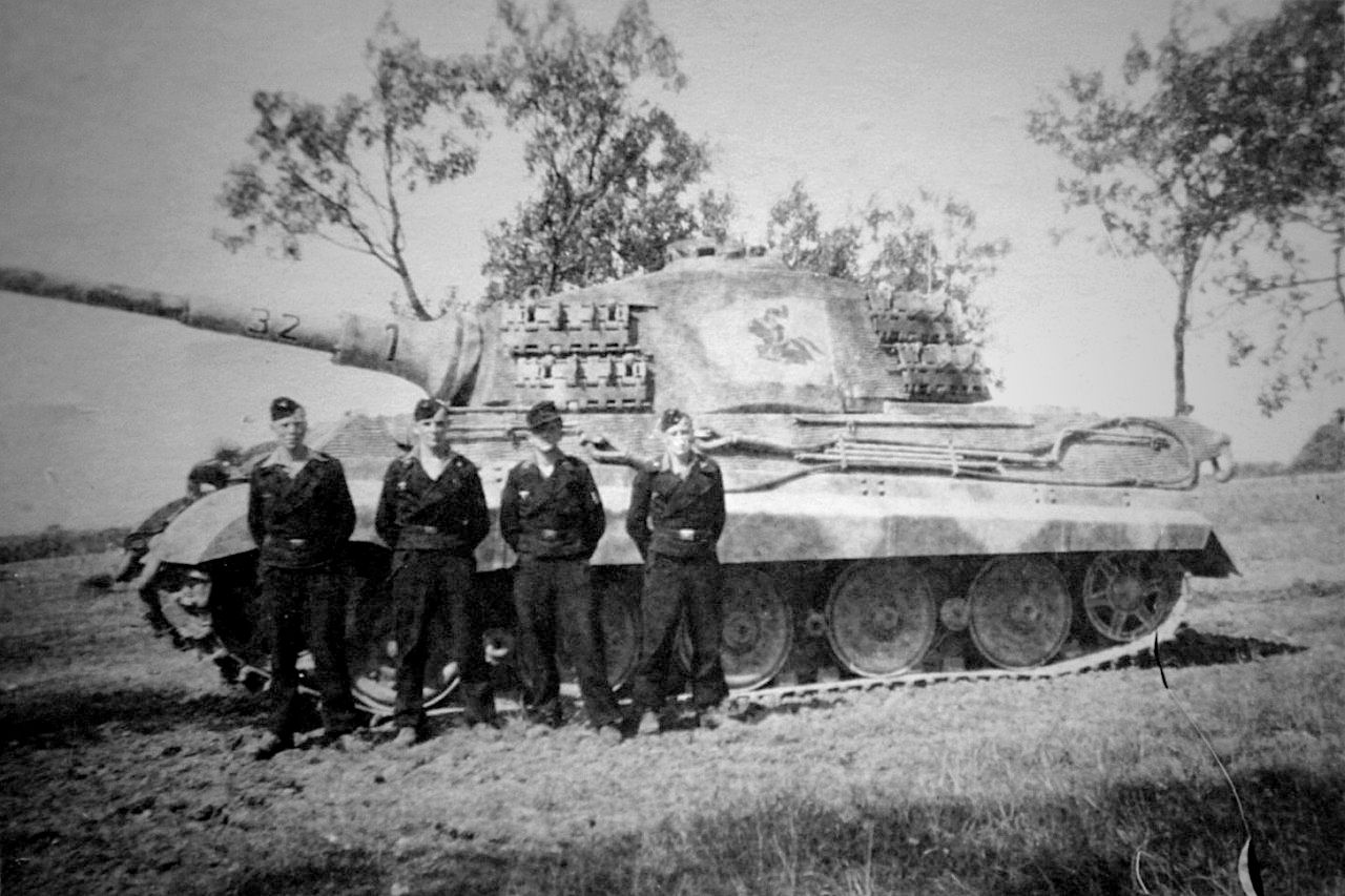 TANKS OF GERMANY - POWER AND STRENGTH.Crewmembers of King Tiger '321' pose in front of their new tank at the Ohrdruf Training Area in August 1944. The insignia of the schwere Panzer-Abteilung 505 (the charging knight) is painted right in the middle of the turret side on a rectangle that is cleared of the Zimmerit paste.