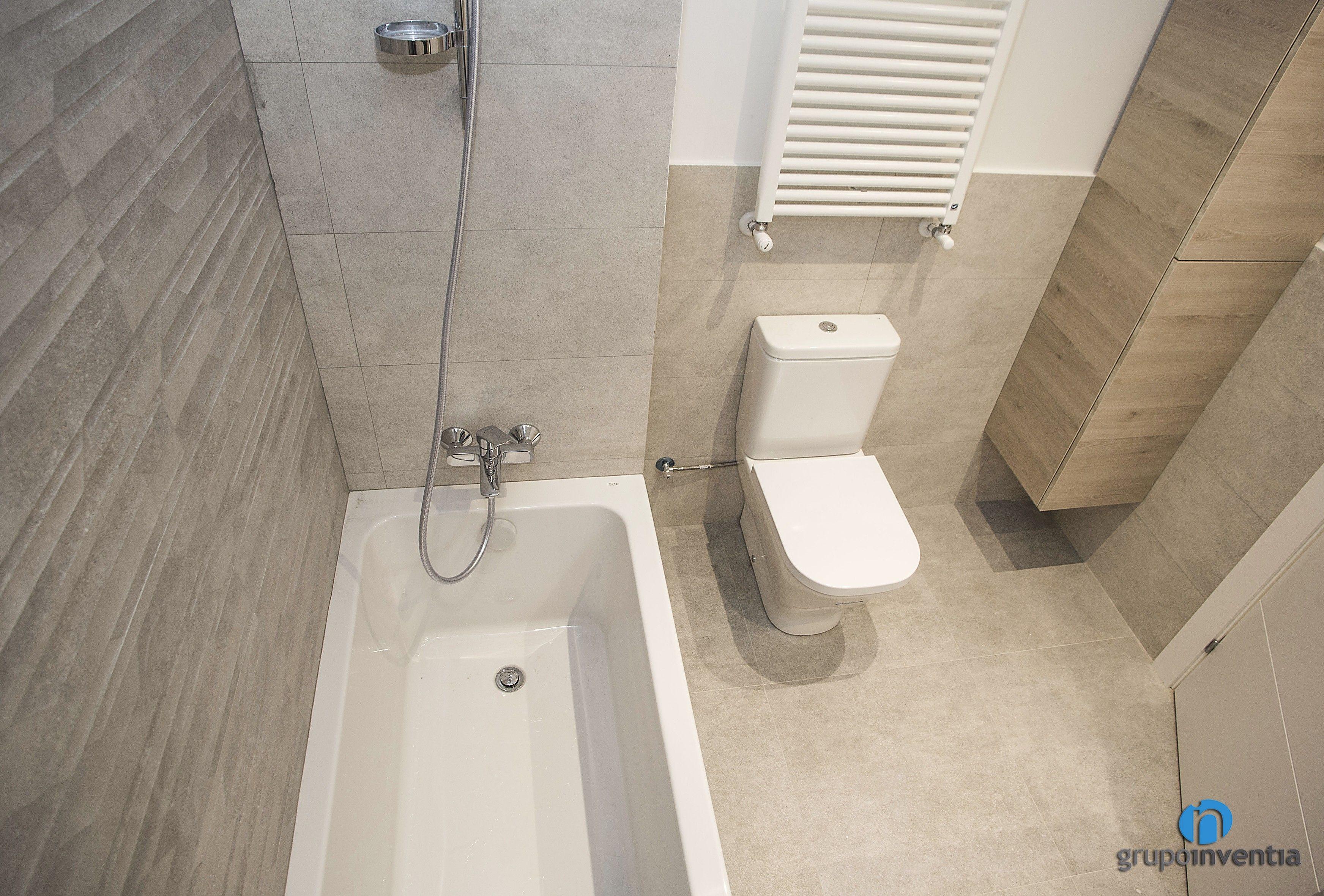 El baño principal de la casa está alicatado a media altura ...
