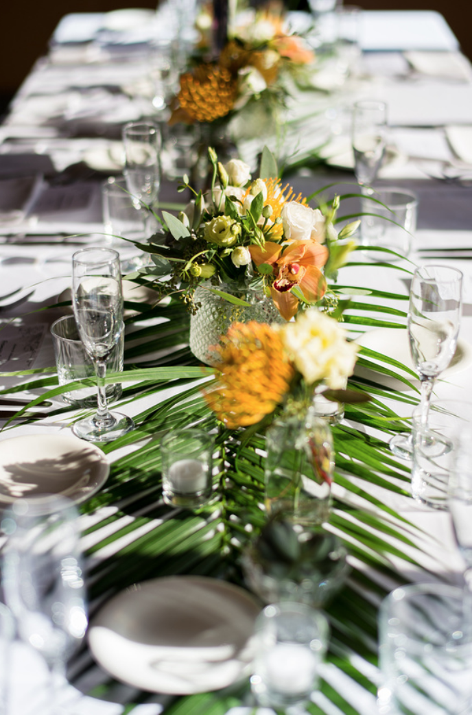 Tropical Dining Table Decor With Palm Fronds Bud Vases Of Tropical Blooms Tropical Centerpieces Bud Vase Centerpiece Candle Arrangements