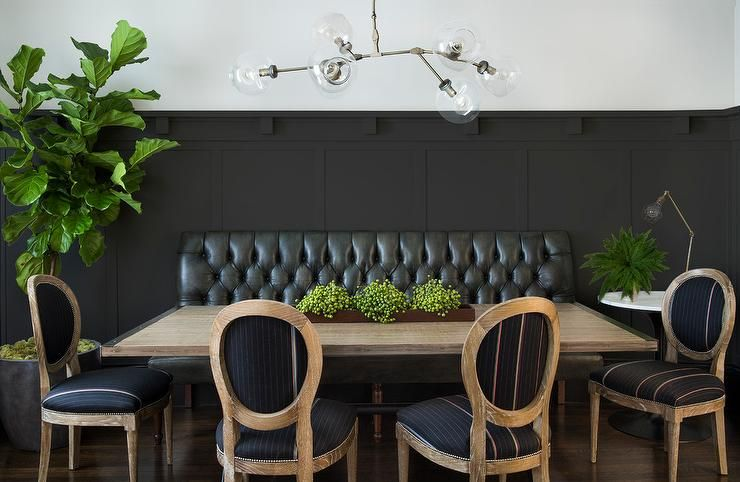 A Black Board And Batten Wall Is Lined With Black Leather Tufted