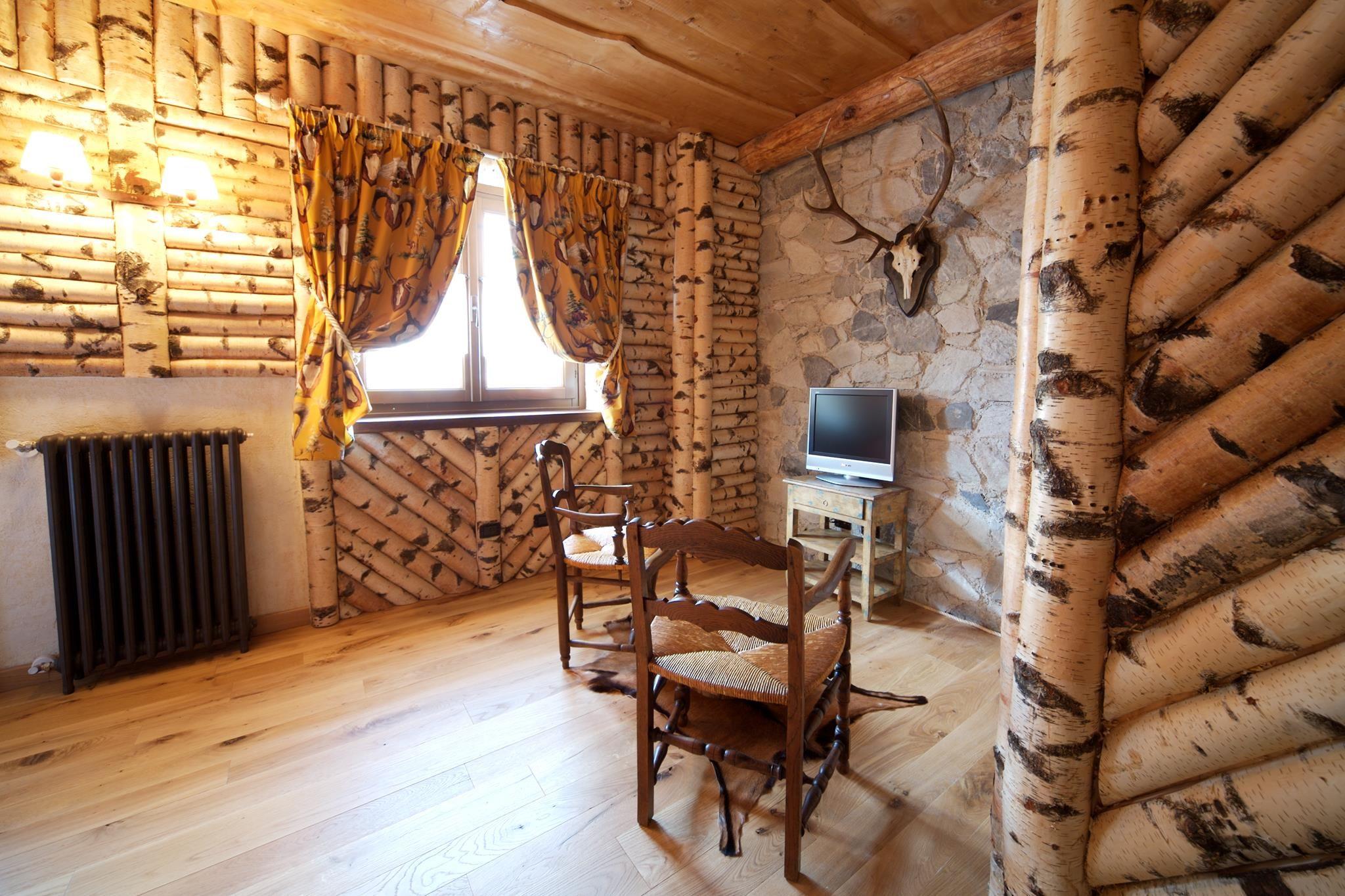 Rivestimento pareti con tronchetti di betulla e soffitto con tavole sovrapposte di cedro ...