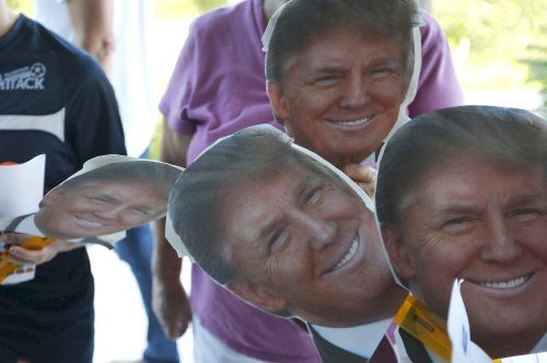The Gallagher family carries cut-outs of U.S. Republican presidential candidate Donald Trump while waiting in line outside a campaign town hall meeting in Derry, New Hampshire August 19, 2015.   REUTERS/Brian Snyder - RTX1OUWQ