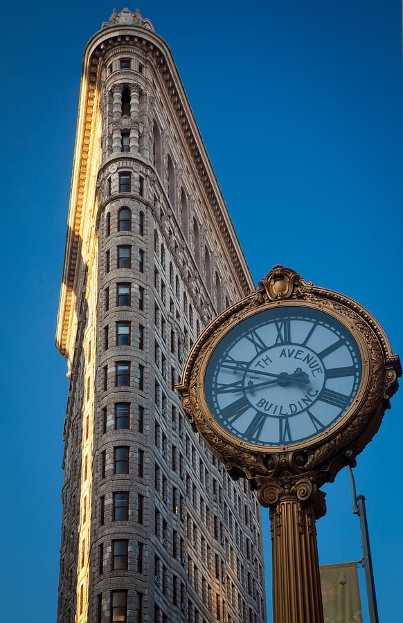 Fifth Avenue Clock and Flatiron Building, Manhattan. The Fifth Avenue Building Clock stands at 19 feet high and is constructed out of cast-iron.