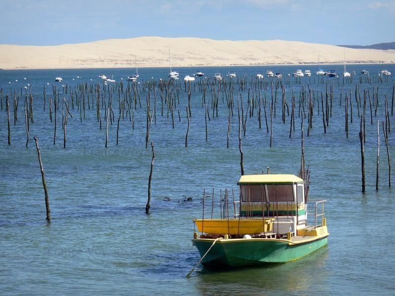 Cap-Ferret: Le Cap-Ferret: Bassin d' Arcachon oester boot met uitzicht op het duin van Pilat - France-Voyage.com