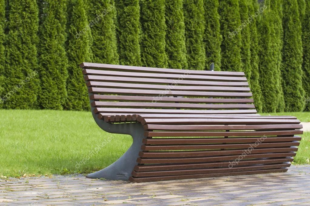 Modern snygg kurva formad brun träbänk utemöbler i parken