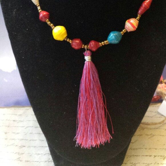 54 to 60 inch paper beaded Uganda beads multicolor necklace ready to ship. Features a tassel in bold shades of burgundy pink. $12 plus shipping. Profits go to Hope Hearts Ministries in Kampala, Uganda.