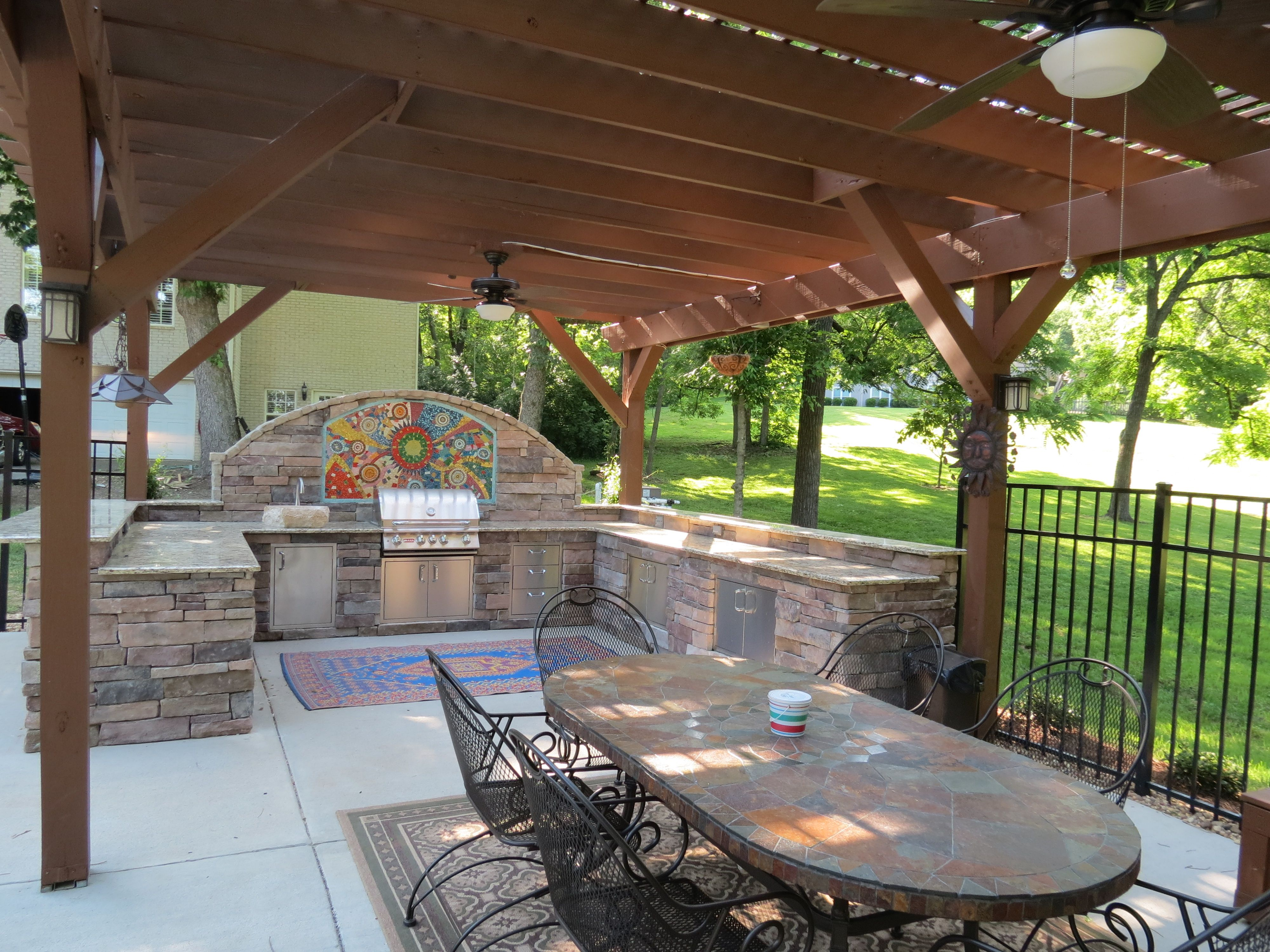 Outdoor kitchen area with grill, sink, refrigerator ...