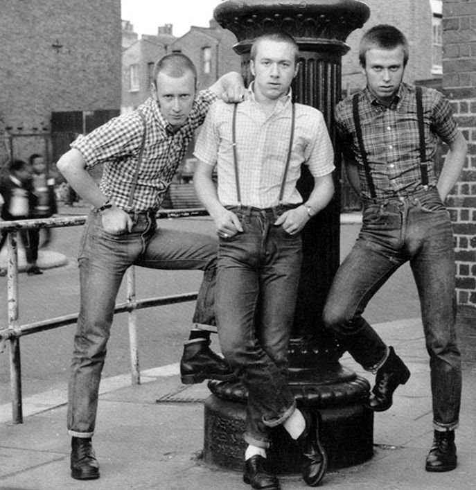 6cc1512259d Cropped hair, braces, short, wide Levi jeans, button-down Ben Sherman  shirts and highly polished Dr. Marten boots (skinheads).