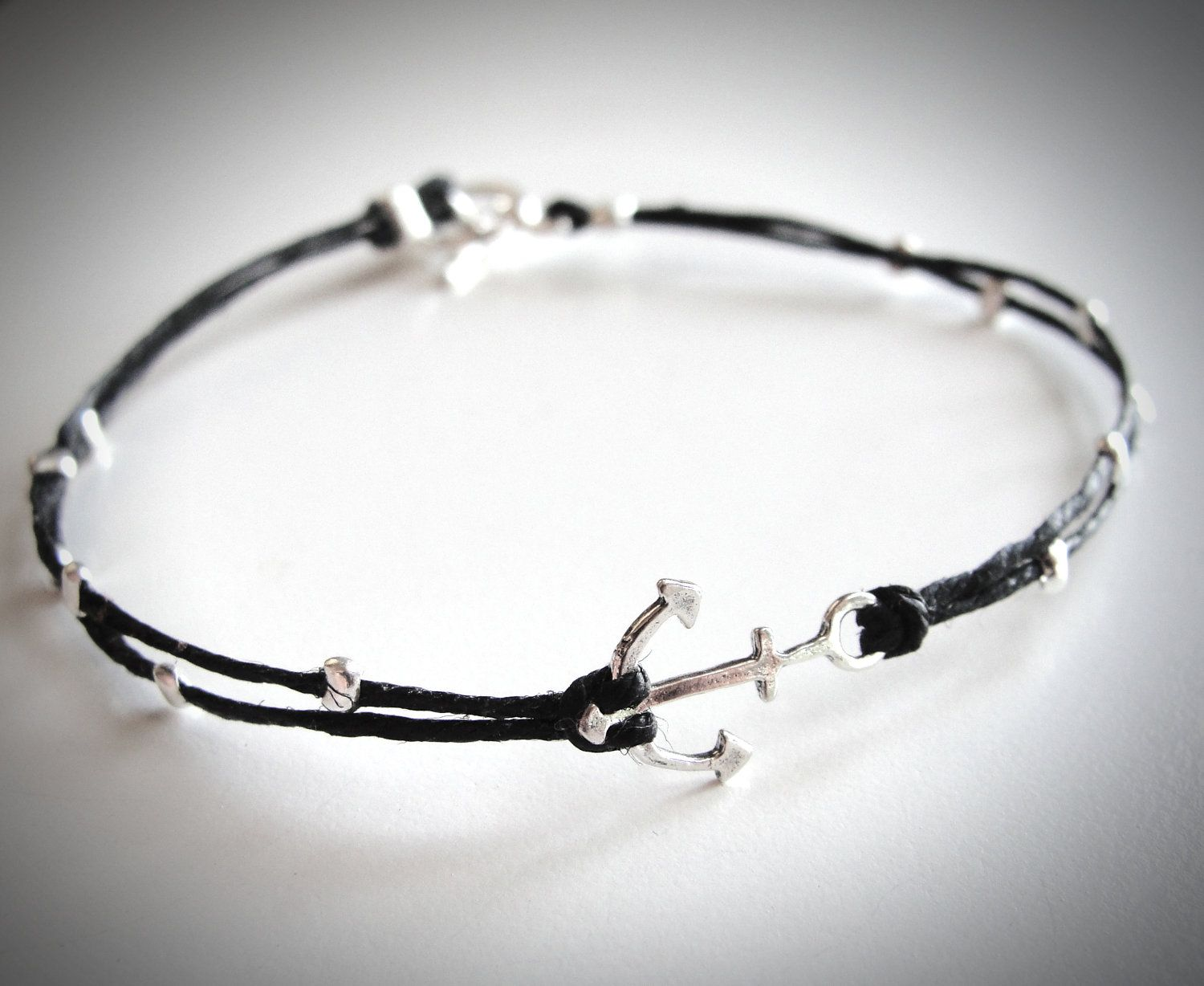 Tiny Sterling Anchor bracelet on black linen. $22 from JewelryByMaeBee on Etsy.