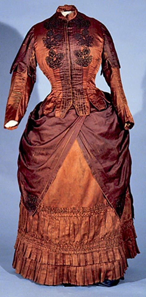 Dress, Canadian, 1882. Brown silk satin bodice, with tucks & couched detailing on front and soutache. Ten-button closure. Short, dagged over-sleeves in darker brown. Watch pocket on left waist. Matching skirt with ruffled bottom. Draped overskirt of darker brown satin with couched stylized floral motif at corners matching those on bodice. Dust ruffle at hemline. Univ. of Alberta