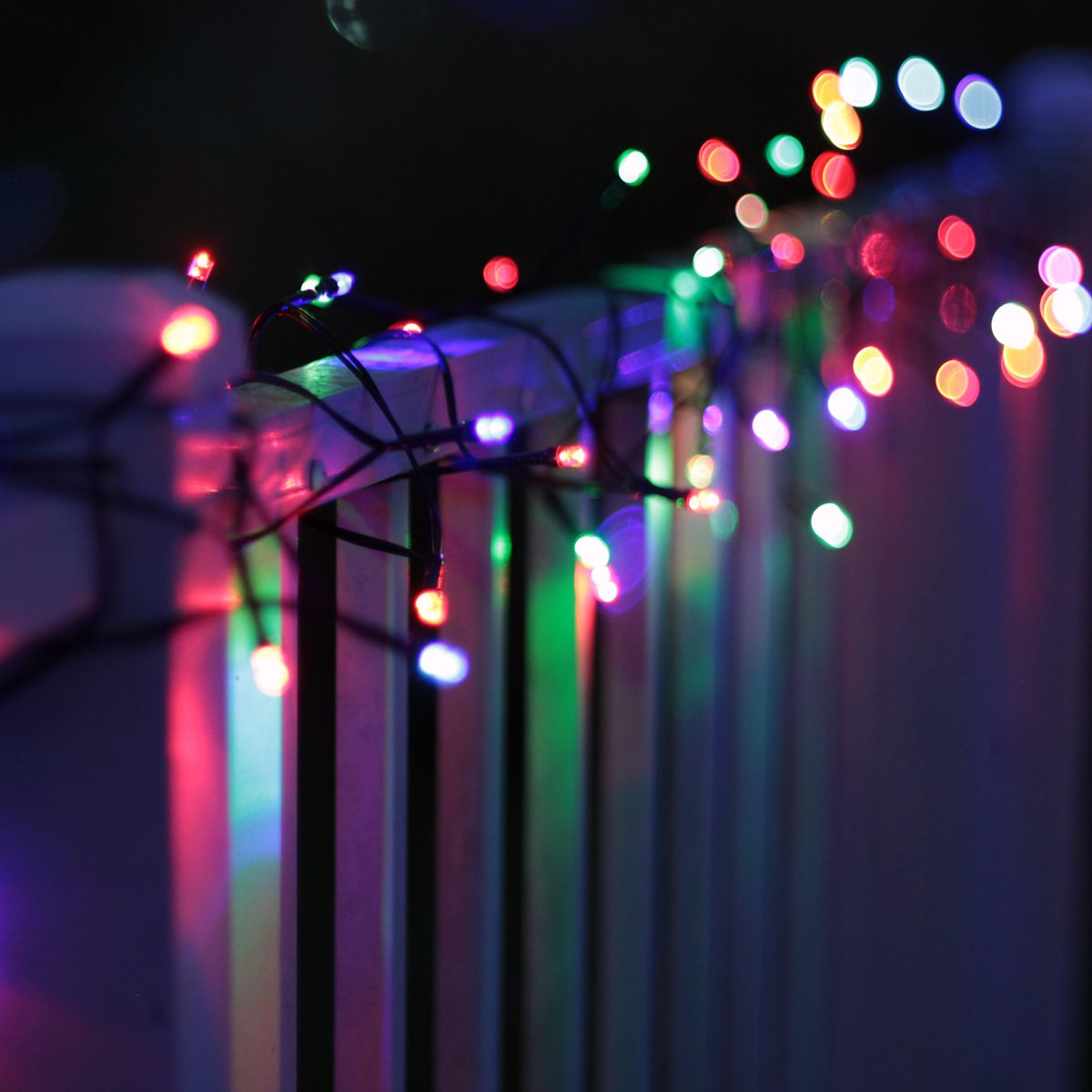 SOLAscape's Color-Changing Solar String Lights (50 LED bulbs on a 22 ft string) adorning a porch ...