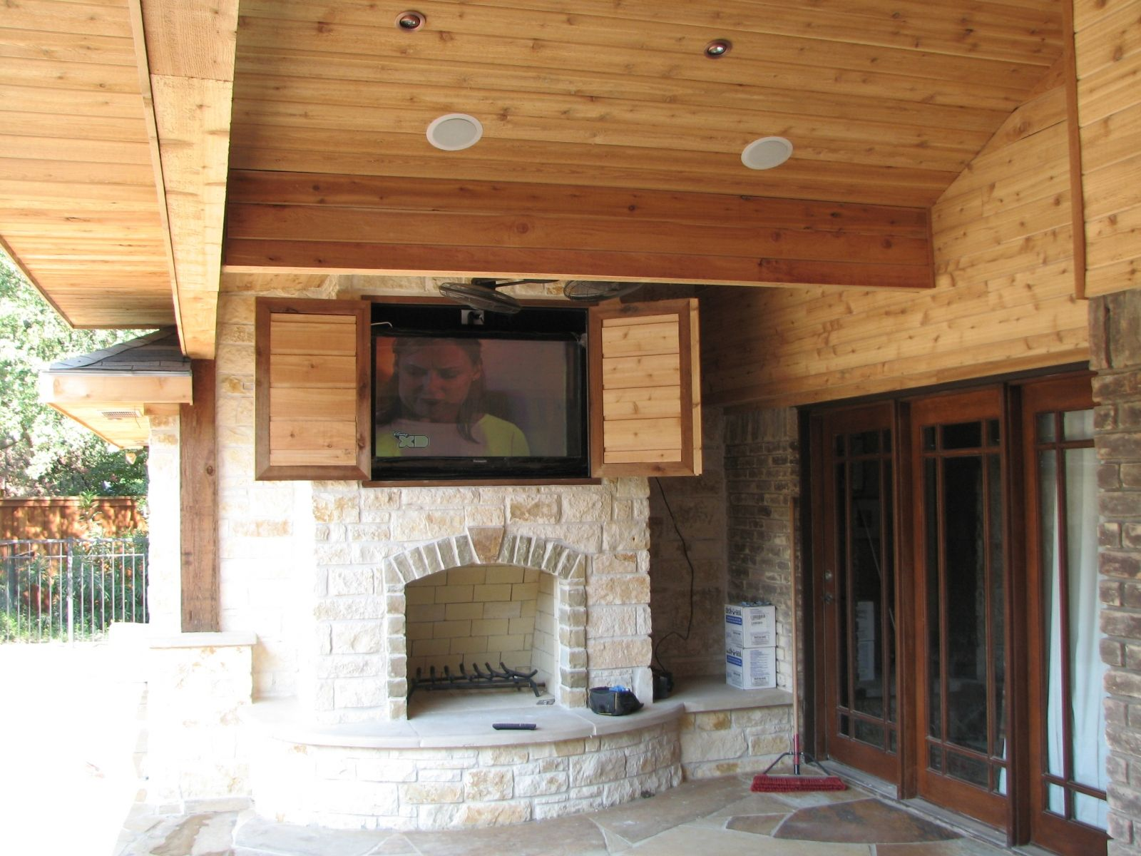 Marvelous Stacked Stone Rustic Fireplace Under Built In Outdoor Tv Cabinet  With Wooden Ceiling Exposed As Inspiring Veranda Decor Ideas