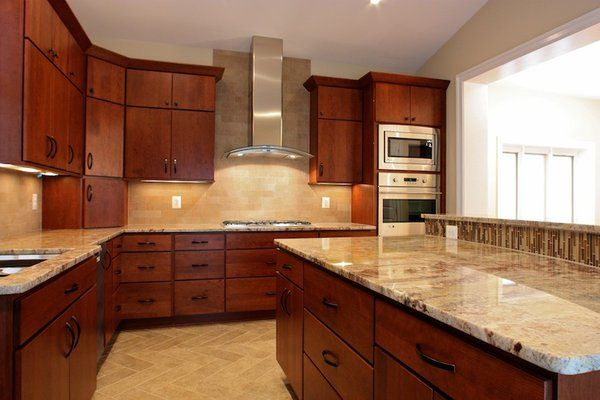 kitchen with a curved granite countertop island stainless - Kitchens With Cherry Cabinets