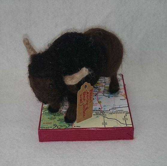 Hand needle felted bison made from Merino wool and Black Suffolk wool on a wooden base decoupaged with a partial map of Alberta (2015) by Holly Boone of Polar Lights Art Studio