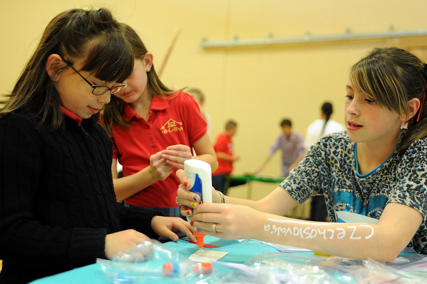 """Second grader Kiara Barney, 8, and fifth grader Hailey Sapanaro, 11, create a Czech Republic flag May 10 at Banning Lewis Ranch Academy in Falcon School District 49. While kindergarten-fourth grade students entered the academy's gymnasium, groups of fifth graders welcomed them to """"European extravaganza."""" They encouraged them to visit their country-themed tables, where they'd present research and stamp """"passports."""" The event started with classroom presentations of slideshows and magazine…"""