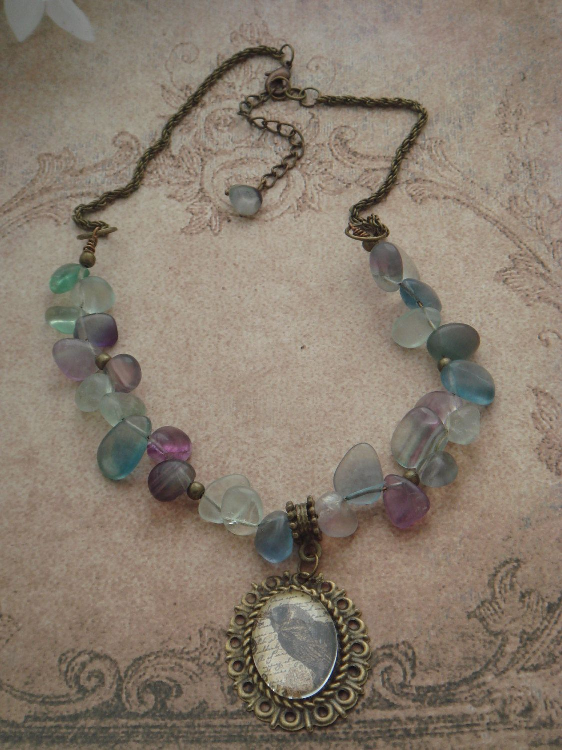 FLUORITE RAVEN NECKLACE Made from Fluorite drops on antique bronze chain, featuring a raven cabochon pendant. £25.00