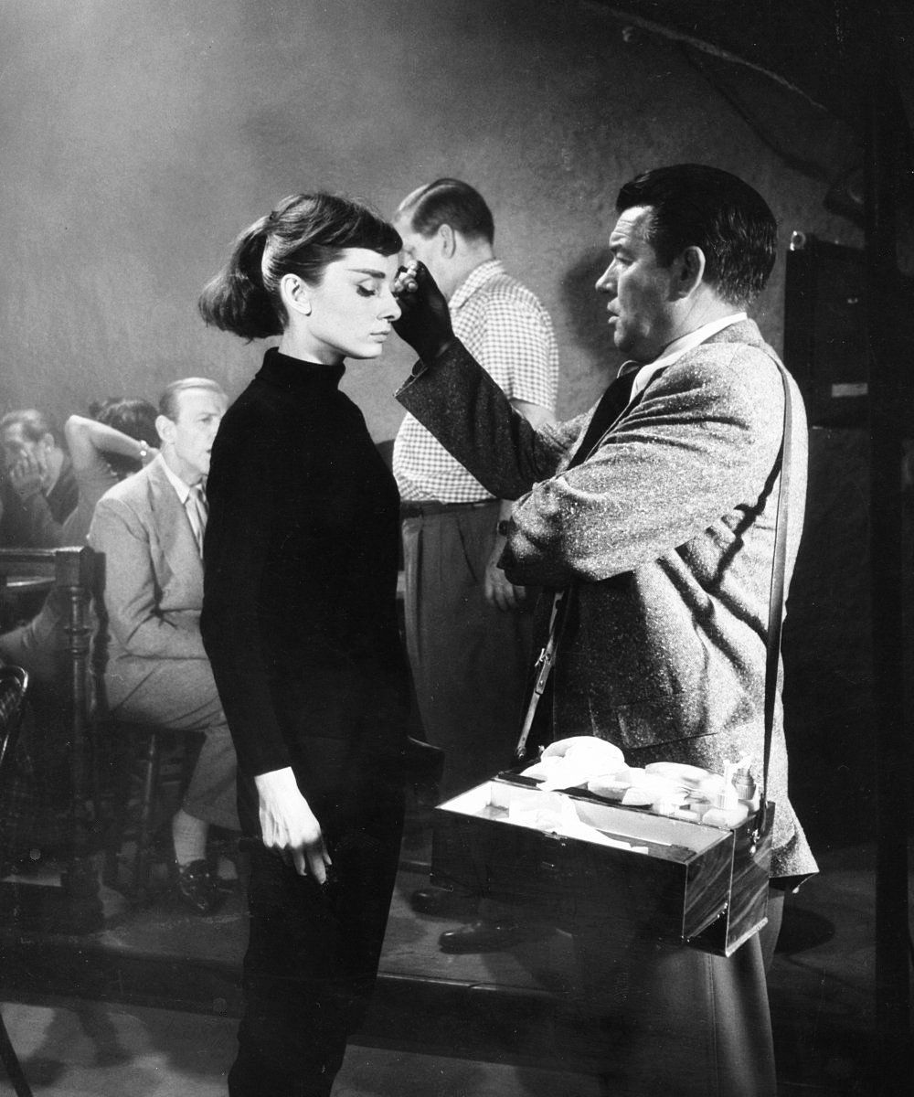 Audrey Hepburn having her makeup touched up by her personal makeup