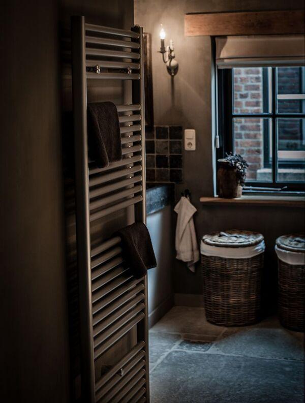 Grijze landelijke badkamer met grijstinten, houten blaken, rieten manden en design radiator. #landelijk #badkamer #bathroom #rustic