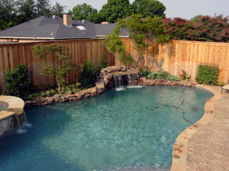 Freeform pool and spa with 6 ton waterfall 3 tons of moss for Custom swimming pool designs
