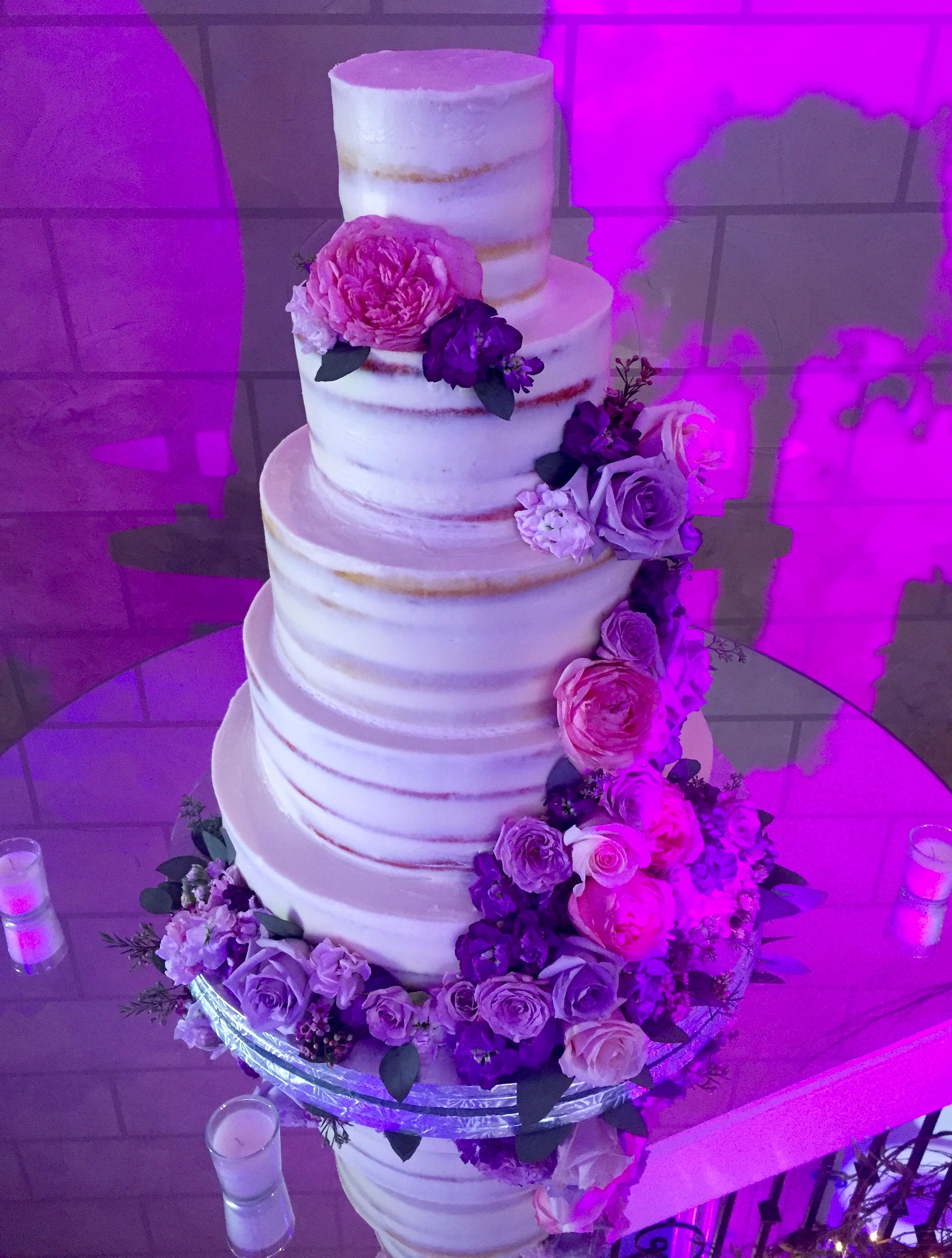 A Beautiful Naked Cake with cascading pink and purple florals ...