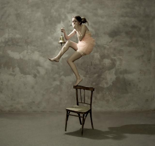A Katerina Bodrunova photograph of a girl standing on the back of a chair ringing a bell