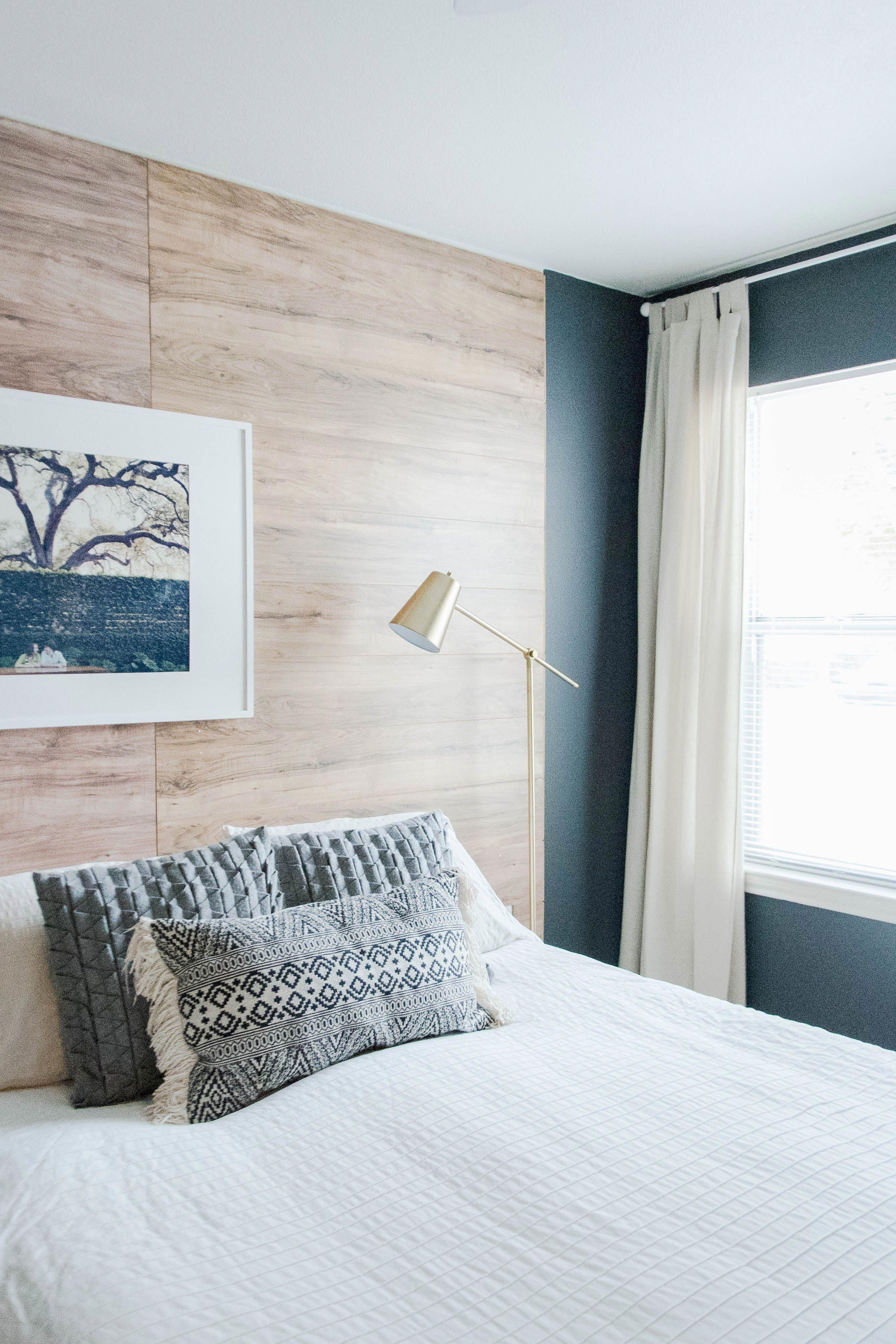 The Dark Blue Walls Against The Soft White Bedding And Wooden Wall Accent Create A Really Peaceful Remodel Bedroom Small Bedroom Remodel Master Bedroom Remodel