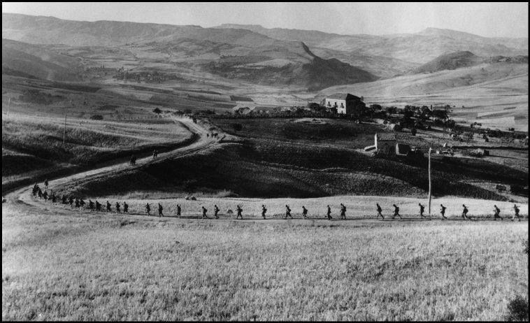 American troops marching toward strategic hilltop town that the Germans had determined to hold at all costs, near Troina, Sicily, August 4-5, 1943 (Robert Capa)